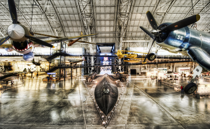 """<h2>The Blackbird in the Hangar</h2> <br/>You may not even really need to be into planes to know about the Lockheed SR-71 Blackbird.  The way those letters and numbers fit together is almost poetic, isn't it?  SR-71.  There is a melody to it that flows in a nice way.  It almost makes me wonder if there is some military muse that comes up with some of the better names for these vehicles.<br/><br/>In the background there, waaay in the rear area, you can see the space shuttle ... <br/><br/> - Trey Ratcliff <br/><br/>Read the rest of this entry <a href=""""http://www.stuckincustoms.com/2010/08/16/blackbird-sr7/"""">here</a> at the Stuck in Customs blog."""