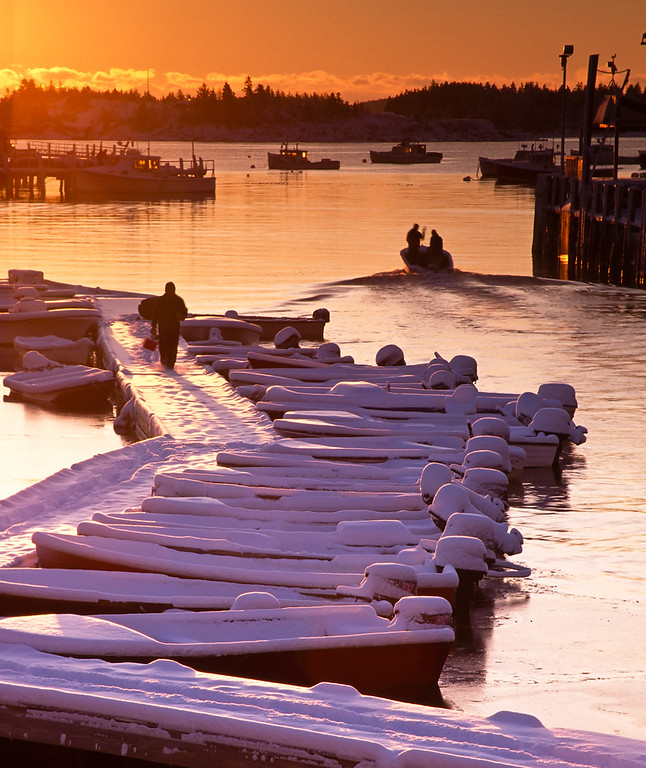 Fishermen head out in their  skiff to the moored lobster boats on an early morning after a big snow fall at the fishing wharf in Stonington, Deer Isle, Maine, USA.