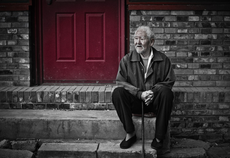 "<h2>Old Man on Steps near Drum Tower</h2> While I was circling the Drum Tower in Beijing, there was a small community of people that were outside exercising, milling around, talking, and watching the world go by.  Many of the homes in the little houtong had their doors painted red, and that was a common element that tied everything together.  I had my hip-shooter with me too so I could capture this one.<br/><br/>- Trey Ratcliff<br/><br><a href=""http://www.stuckincustoms.com/2012/04/25/23249/"" rel=""nofollow"">Click here to read the rest of the post at the Stuck in Customs blog.</a>"