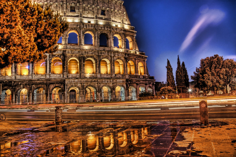 """<h2>Aurorus Reflectus Colosseo</h2> <br/>Ahhh Rome!  I love it there.  Everywhere I walked was filled with art and inspiration.  One of my hobbies is ancient Roman history, so the city had forever held a mythical romanticism place in my mind.  I have a bad (good) habit of circumnavigating structures before taking photos to find the right angle.  I say bad because some of these structures are so big that it's a major commitment to walk around the thing.  Finally, however, it paid off and I found some wet pavement just outside one of the subways.<br/><br/>That purple streak in the upper left is very mysterious.  I don't really remember what happened during the shot to cause that, but it was an unexpected and pleasant surprise.<br/><br/>- Trey Ratcliff<br/><br/><a href=""""http://www.stuckincustoms.com/2006/08/04/colosseum-reflected/"""" rel=""""nofollow"""">Click here to read the rest of this post at the Stuck in Customs blog.</a>"""