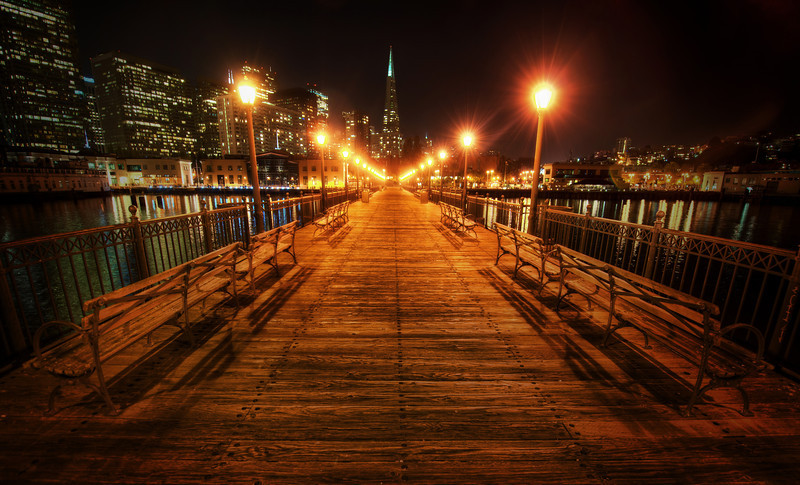 """<h2>The Long Dock</h2><br/> On one of my final nights in San Francisco, I walked out on the dock off the Embarcadero to see what I could see.  There were nice views in every direction, and one of the best was looking straight back up the dock at the Transamerica building.<br/><br/>This wide-angle 14-24 lens is one of my favorites, but it does have one little problem that can also be an advantage.  It takes whatever is in the center of the frame and makes it quite small.  The opposite of that happens on the edges, where things get quite spread out.  So, I did that little trick here to help the Transamerica building to seem a bit taller.<br/><br/>- Trey Ratcliff<br/><br/><a href=""""http://www.stuckincustoms.com/2012/04/12/the-long-dock/"""" rel=""""nofollow"""">Read the rest of this entry at the Stuck in Customs blog</a>"""