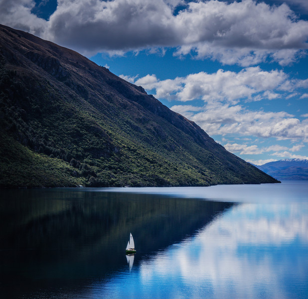 """<h2>Sailing on Lake Wakatipu</h2> <br/>The car trip started here in Queenstown on Lake Wakatipu. It was a perfect spring day, and there was a lone sailboat down on the lake. Everything is on such a big scale here, maybe you can get a sense of the overall size of the lake from the tiny sailboat on there… it looks like a toy!<br/><br/>- Trey Ratcliff<br/><br/><a href=""""http://www.stuckincustoms.com/2012/11/04/more-from-the-new-zealand-car-trip/"""" rel=""""nofollow"""">Click here to read the rest of this post at the Stuck in Customs blog.</a>"""