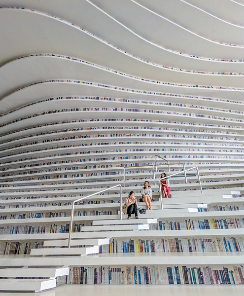 Three Girls Sit In An Impossible Library