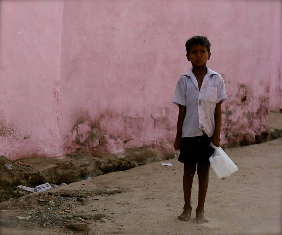 An Indian boy in a peculiar pose, taken in the small village of Jojawar in Rajasthan, India. <br /> <br /> When he saw me with my camera he was excited to be captured, and immediately stuck this pose that I quickly became accustomed to and would see throughout my journey through India.