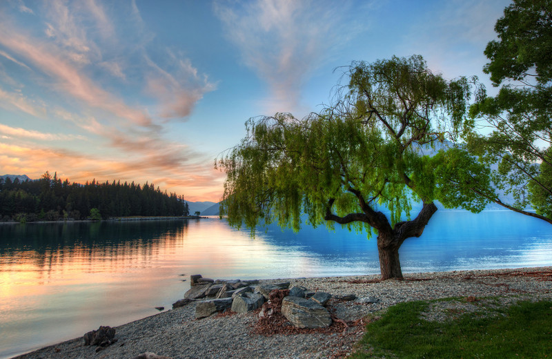 "<h2>Tree at the Serene Lake</h2> Queenstown, I miss you!  The summer here in Texas has been bitter-hot.  I remember the long run I had along your shores...  comparing that with my 100-degree run here in Texas that just makes me want to curl up into a fetal ball and cry...  When I was there in Queenstown, I took to waking up about an hour before the sunrise and brewing a whole pot of coffee.  And then, I would just the take the POT in the car with me and drive around.  The lake can be pretty still in the morning, and that is when I grabbed this one... I'm jealous of my friends Gordon Laing and Eden Brackstone who get to spend almost every day in these environs!  - Trey Ratcliff  Read more <a href=""http://www.stuckincustoms.com/2011/06/07/tree-at-the-serene-lake/"">here</a> at the Stuck in Customs blog."