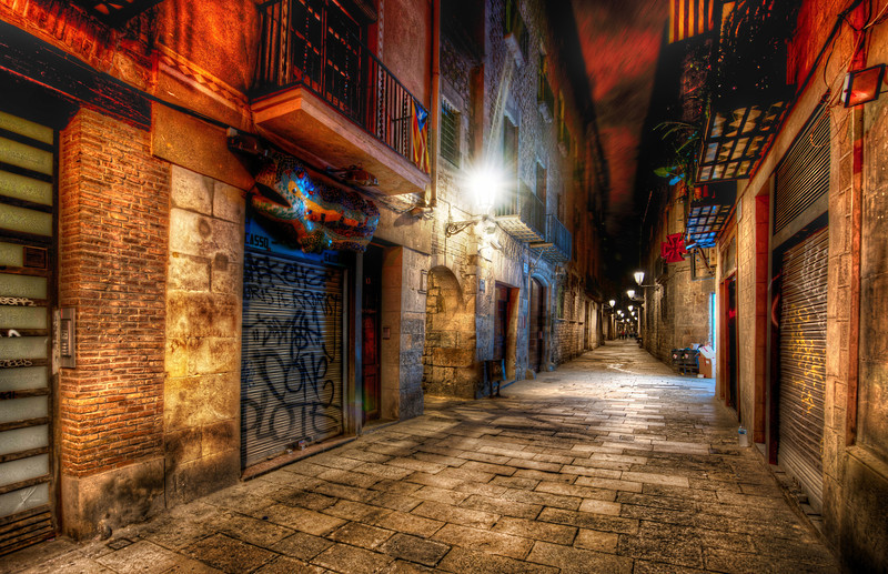 The Endless Alley The dirt and grit and color that comes with European alleys make for great subjects for dynamic night photography.  Usually I only stay out for about an hour after it gets dark, but it's hard to stop with this kind of scenery...  I mean, you can make a legitimate excuse to stay out all night!  But a lot of people warned me about how dangerous Barcelona can be...  I did already meet many people that were robbed blind...  I was extra-extra careful... and, in this case, decided to head back to the hotel early.  Also, I was feeling pretty under the weather...so yet another excuse.  - Trey Ratcliff  Read more, including my top-five Instagram list,  here at the Stuck in Customs blog.