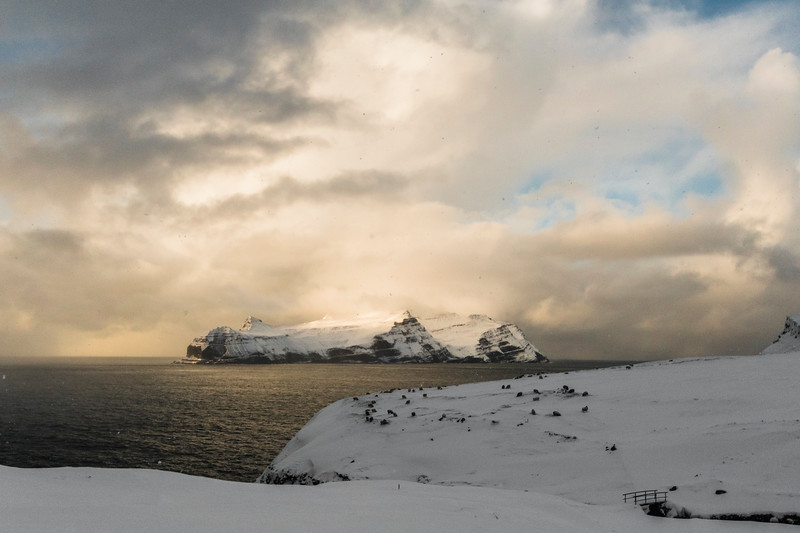 Mykines island covered with snow clouds at sunset