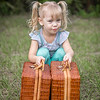 Little girl in pigtails lifting baskets