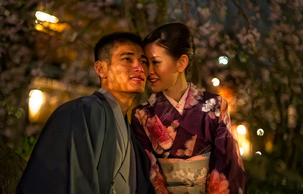 Under the Cherry Blossoms I spent a while one evening in the older Gion district of Kyoto.  Everything was in full bloom and there were all kinds of interesting people and things to see.  It was a bit like a perfect little Japanese fairy-land.  When the breeze came along, the blossoms would fall loose and flutter down like pink soft snow.  I saw this couple sitting on a small stone wall beside a little stream under some cherry trees…I did my best to blend into the background as I slyly slid inwards with my D3S.  This was shot at ISO 3200, and you can see how little noise/grain there is in the exposure.- Trey RatcliffClick here to read the rest of this post at the Stuck in Customs blog.