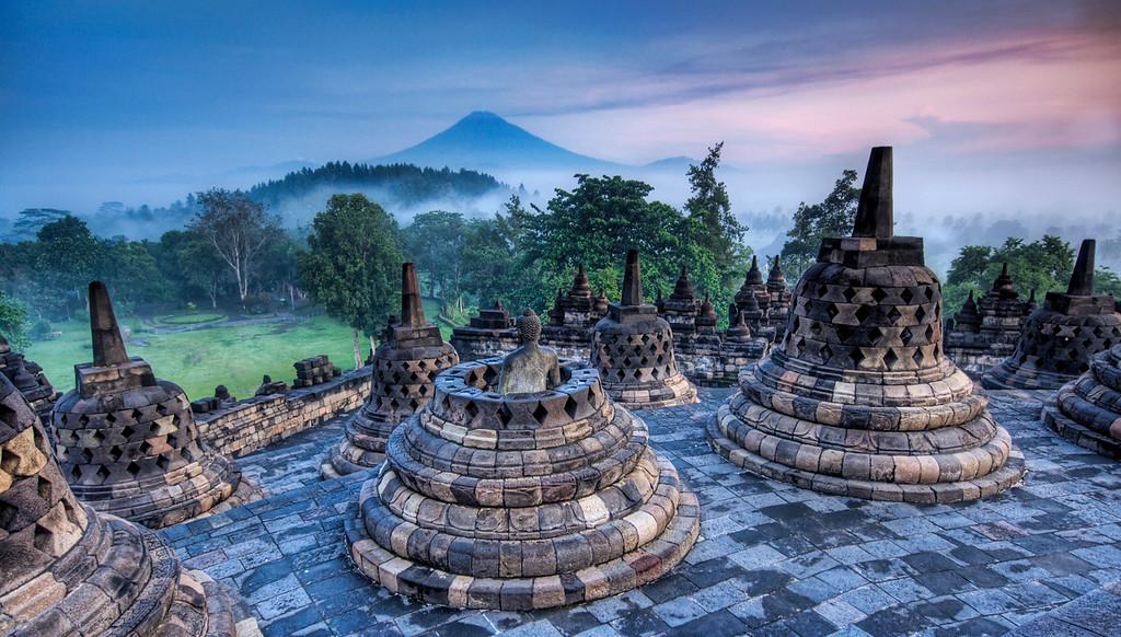 The Hidden Buddhist Temple of Borobudur at Sunrise This morning I got a wakeup call at 3:30 AM to head out on a distant trek to Borobudur to climb the temple before sunrise.  I had a flashlight and a fully loaded iPod for the ascent.  I stayed at the top and all around the temple for most of the morning, collecting shots here and there as misty clouds rolled in, through, around, and over the temple.This temple laid abandoned and overgrown for about 800 years until it was rediscovered by the British.You can see the distant volcano rumbing in the morning sunrise...- Trey RatcliffClick here to read the rest of this post at the Stuck in Customs blog.