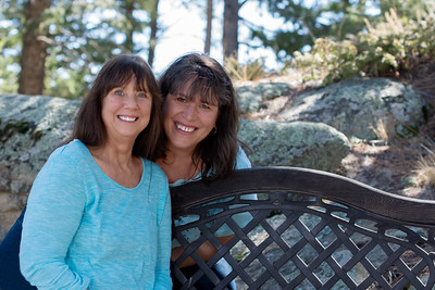 Portrait of two joyful women with dark hair and light blue blouses, sisters, sitting on an iron bench with rocks and trees in the background.