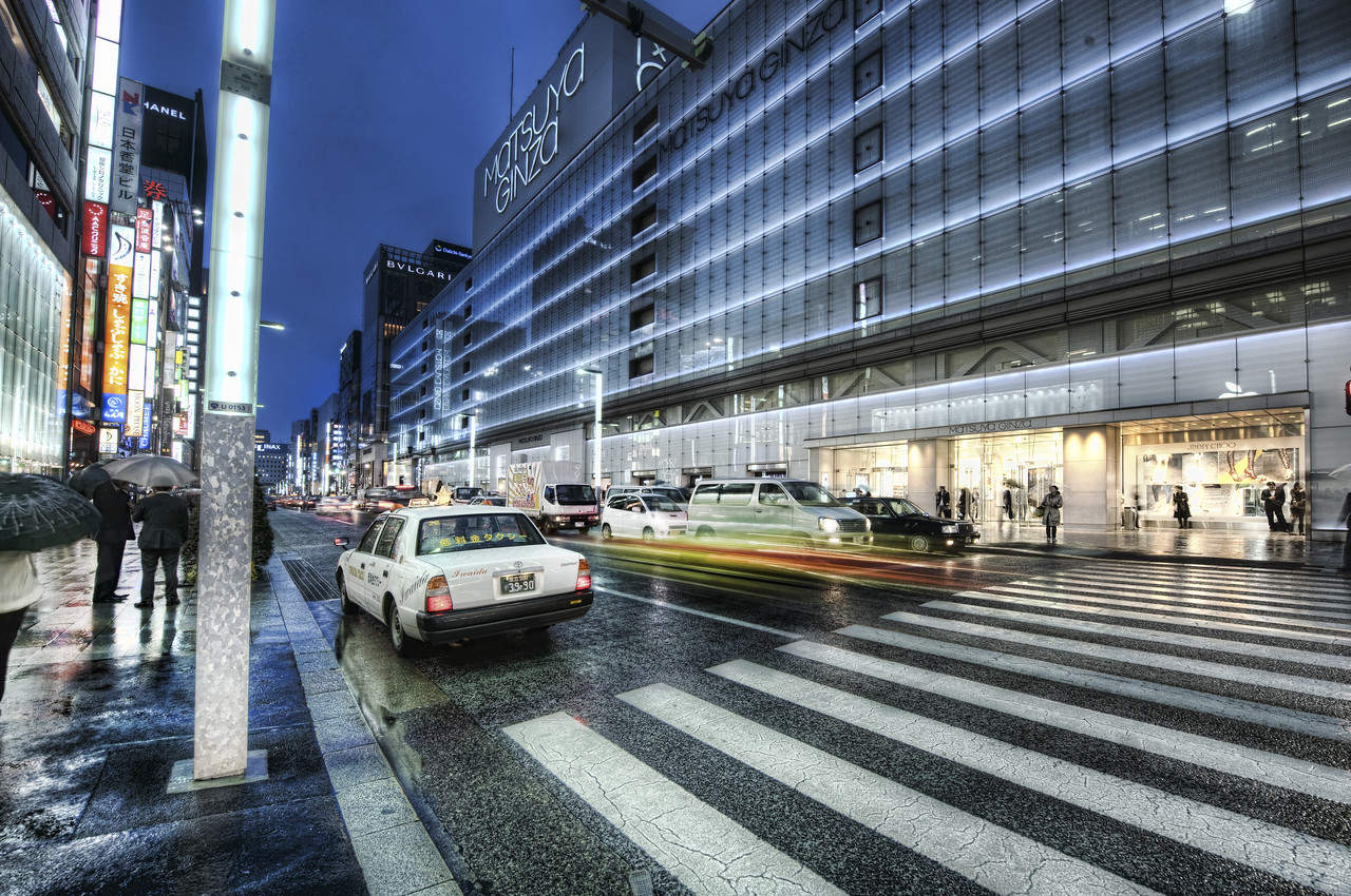 Ginza, alive at night Rain is good.  Rain is bad.  I can't decide!You have no idea... (or maybe you do !!) how hard it is to carry around two cameras, a tripod, AND an umbrella.  I already have every one of my 10 digits fully employed with handling everything.  But... an umbrella!  Well that really requires five fingers!  I can usually get by with 5 on my tripod/camera too.  I walk around with everything hooked together.  However, a problem ensues when you have to expand and retract the legs of the tripod.  That is really a two-hand operation.  So what do you do with the umbrella during this time?  The neck/shoulder pinch is right-out...  the umbrella gets caught in the wind and it is a recipe for disaster.- Trey RatcliffFrom this entry at stuckincustoms.com.