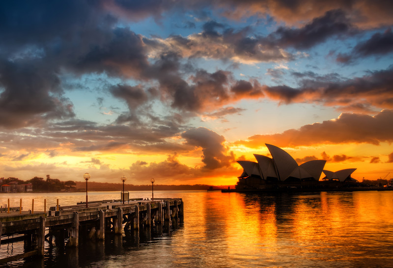 "<h2>Opera House and the Docks</h2> <br/>I took this bright and early one morning when I forced myself to get outta bed and go for a walk. I was feeling particularly lazy that morning and was oh-so-comfy in bed. I was sharing a room with a friend, and I didn't want to wake him up. It's very difficult to wake up, get dressed, and get all your photo equipment together while staying quiet! The only thing I was missing was a cheery assistant there with a cup of coffee. Maybe I should recruit some Starbucks barista to be my assistant – they are always hauntingly cheery and near-coffee.<br/><br/>- Trey Ratcliff<br/><br/><a href=""http://www.stuckincustoms.com/2013/01/02/coming-back-to-australia/"" rel=""nofollow"">Click here to read the rest of this post at the Stuck in Customs blog.</a>"