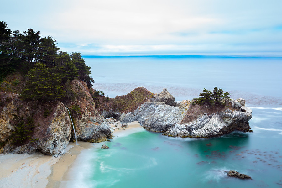 The McWay Falls of Big Sur California Off Highway 1 on the South end of Big Sur California is this epic view of McWay Falls. The color of the water and the rocks here against the sand is really a surreal view. Such an epic spot in one of the most beautiful drives in the world.