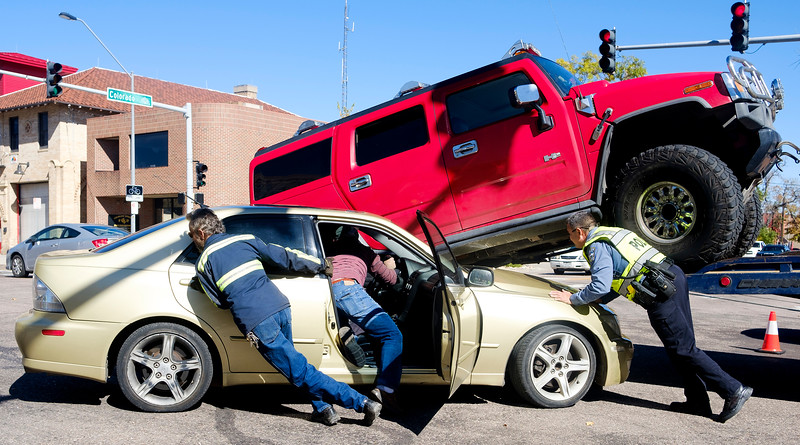 Steve Denney, in the car, steers his Lexus while a tow truck driver and police officer push it out from under the Hummer that drove over it in the intersection of Colorado Ave. and Weber St. on Tuesday, Oct. 10, 2017. No one was hurt in the accident.<br /> <br /> (The Gazette, Nadav Soroker)