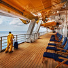 "<h2>Swabbing the Decks</h2><br/>The Disney Cruise aboard the Fantasy had deck after deck after deck – something was always happening – everywhere! It was pretty stimulating as a photographer to try to figure out where to be at different times.<br/><br/>This is the deck where the running track is. It goes around the outside of the ship, and I like to run so I was out there almost every day. I noticed around a certain time that these guys come out in yellow outfits to swab them down. So I made a point to get out there the next day and set up for this image.<br/><br/>- Trey Ratcliff<br/><br/><a href=""http://www.stuckincustoms.com/2012/06/13/swabbing-the-decks/"" rel=""nofollow"">Click here to read the entire post at the Stuck in Customs blog.</a>"