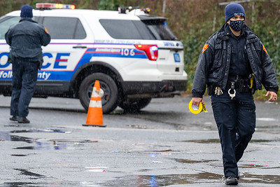A Suffolk County Police Officer tapes off a crime scene on a cold and wet day, shortly after a shooting in Wyandanch. 12-25-2020