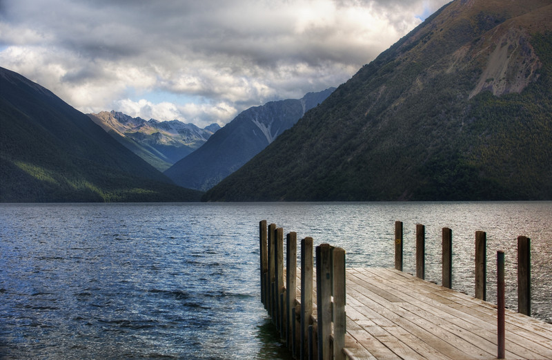 "<h2>The Dock to Forever</h2> <br/>One of the advantages of going down all the side roads is that you get to find cool places!  After leaving Nelson on the South Island, we found a little lake on the map that looked about perfect.  After a few hours of meandering, we discovered this place was almost completely empty (just like every place else on the South Island!).  Even better, there was a perfect little dock jutting out into the lake.<br/><br/>I first took a bunch of shots with my 14-24mm lens...  but it was not really getting the dock with the distant valley in the right way.  So, I put on my 70-200mm, zoomed in almost all the way, then backed up quite a bit to get the compression effect of the valley.  Remind me to post the other version someday so you can see the comparison!  I haven't processed it yet -- but it is in my ""Pile to Process"" -- which is now 22,000 strong.<br/><br/>- Trey Ratcliff<br/><br/><a href=""http://www.stuckincustoms.com/2010/03/23/the-dock-to-forever/"" rel=""nofollow"">Click here to read the rest of this post at the Stuck in Customs blog.</a>"