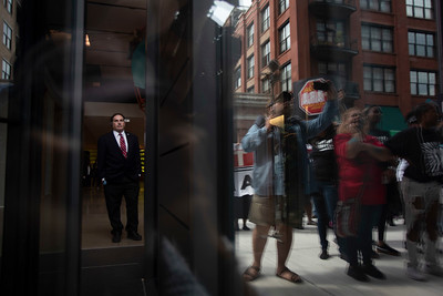 A man watches from inside as protesters carry a list of demands outside the McDonald's headquarters in the West Loop neighborhood of Chicago during the one-day strike over sexual harassment led on September 18, 2018. | Colin Boyle/Sun-Times