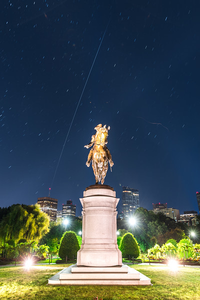 Int'l Space Station flying into the horizon over the statue of George Washington in the Boston Public Garden.