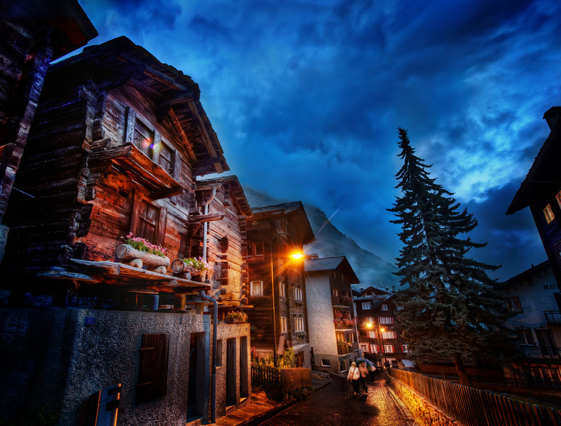The Streets of Zermatt After dinner one evening, I went out with my iPod to explore the streets alone.  There was a light cool rain, but it didn't bother me a bit.  It added to the mood and everything felt great.  The warm cabins, the cool sky, the wet streets, people hurrying to and fro to get warm food and drinks...  I do my best to capture this feeling all in one image.  - Trey Ratcliff  See the rest of this blog entry here at stuckincustoms.com.