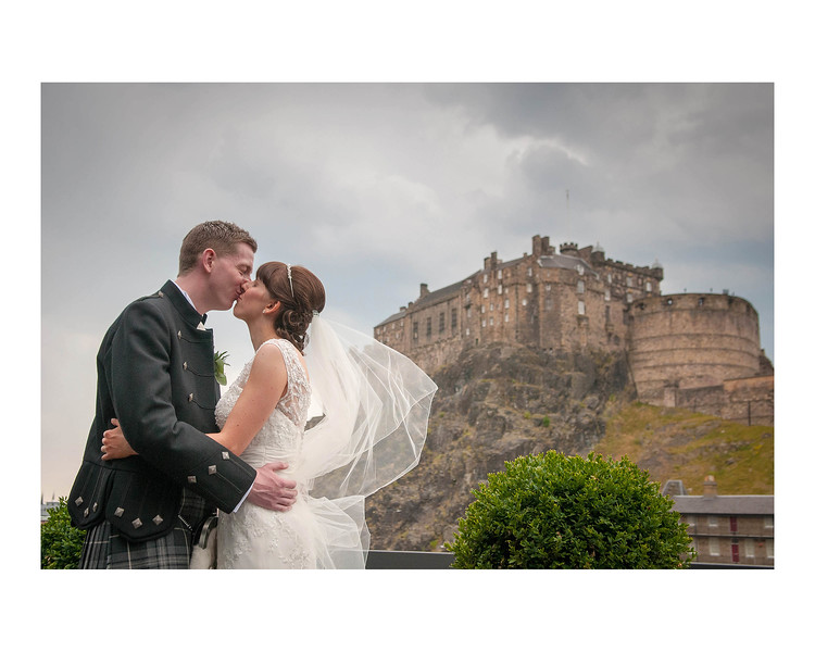 Wedding Photography of Laura & Paul, Apex International, Grasmarket, Edinburgh, Scotland, Photograph is of the Bride & Groom having a kiss on the Apex balcony with Edinburgh Castle as a backdrop