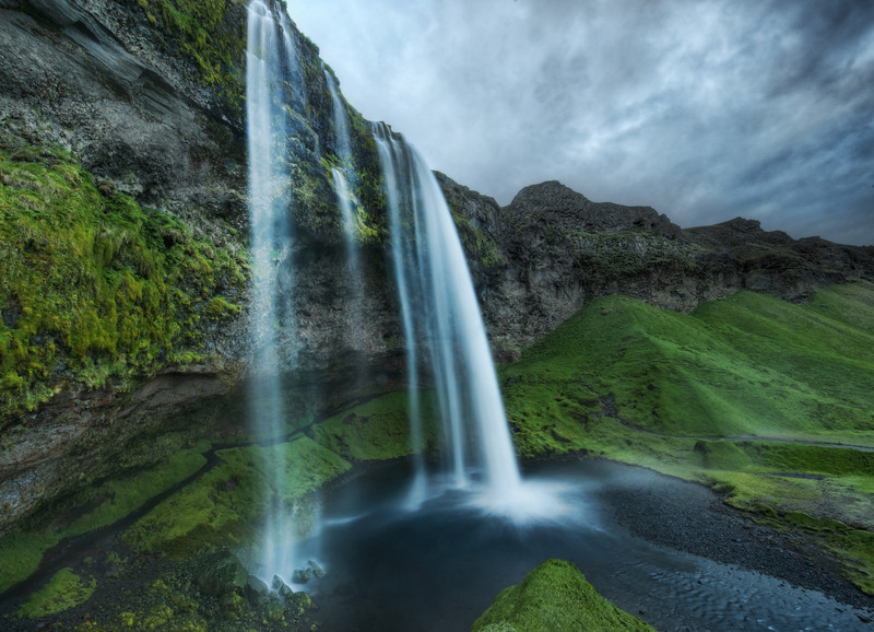 "<h2>Waterfalls at Midnight</h2> <br/>I had done a little research about the southern part of Iceland before my trip, but I left enough gaps to be surprised. <br/><br/>On this particular night, it was about 65 degrees (18 C), so it was just a tad perfect.  The air was wet with moisture from an evening rainstorm, and it was held aloft by the strange weather patterns.  When I first saw this waterfall, it was around midnight.  By the time I got into this position, it was about 1 AM or so.<br/><br/>Once again, I had not seen another human for hours.  It was so eerie walking around these amazing places alone.  Typically, with something so grandiose, you sort of expect a bunch of tourists to be lurking about.  So, alone, it all feels a bit post-apocalyptic.  But thanks to a ton of video games, I'm well versed with how to survive in these situations.<br/><br/>- Trey Ratcliff<br/><br/><a href=""http://www.stuckincustoms.com/2010/10/22/waterfalls-at-midnight/"" rel=""nofollow"">Click here to read the rest of this post at the Stuck in Customs blog.</a>"