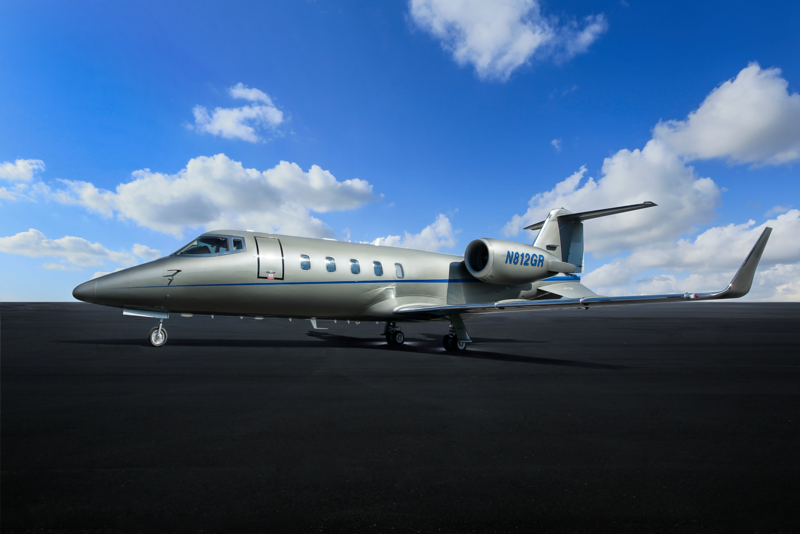 Exterior aircraft photo with gloss silver finish and blue trim lines in a clean, almost futuristic scene. Note the hint of cloud movement in the background daytime sky. This look can be created even with shoots at the busiest locations.