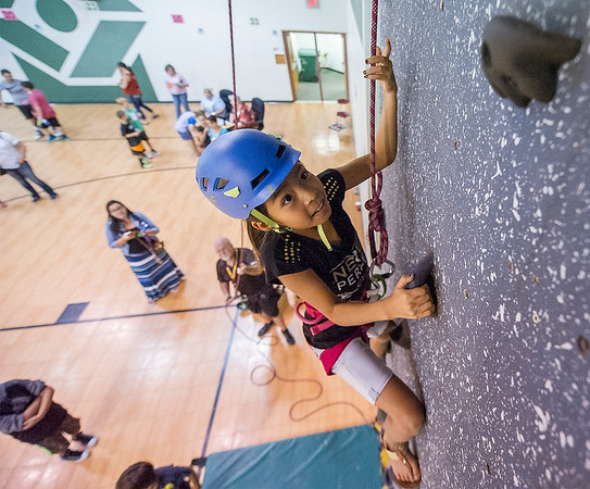 Kathya Guillen, 10, looks to the next hold on the climbing wall at Charles O. Stones Intermediate Center during the Health Night event Thursday. Children participated in healthy snacks and activities encouraging exercise.