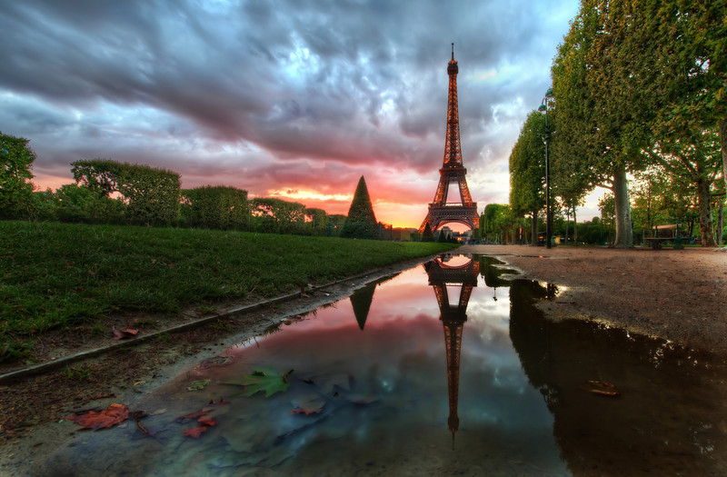 Reflections on the Eiffel Tower Isn't it romantic?  What could be more perfect than a beautiful sunset here in Paris?There was a big storm all day long, but I could see the clouds were beginning to break up a little to the west, and I knew there was a possibility the sun would dip into an opening beneath the heavy clouds.  So, with that intense possibility, I headed over to the Eiffel Tower area hoping the light would turn out right...I also made a behind-the-scenes video.  Since you guys have been so nice over on Google+, I'll share that video exclusively there first, so be sure to stay tuned... I'm still editing the thing together!- Trey RatcliffRead more here at the Stuck in Customs blog.