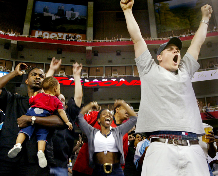Season ticket holder, Josh Faulk, right, celebrates the Atlanta Falcons' first touchdown of the 2002 season with Pat Harris, center, 10-month-old Faren Roberson and Michael Roberson, left, on Friday, Aug. 9, 2002, during the pre-season game against the Jacksonville Jaguars. Atlanta won the game.