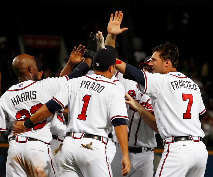 070814 - ATLANTA, GA -   Braves Willie Harris, left, (cq) is congratulated by teammates, including Martin Prado, #1, center, (cq) and Jeff Francoeur, right, #7, (cq) after scoring on Chipper Jones' 9th inning at bat against the Giants on Tuesday, Aug. 14, 2007.  Braves win 5-4.  (JENNI GIRTMAN/AJC STAFF)