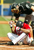 During his at bat, Andrew Jones, bottom, takes a seat after a swing and hands Florida Marlins' catcher Matt Treanor, top, the ball Sunday, Sept. 25, 2005. Braves won against the Marlins 5-3.