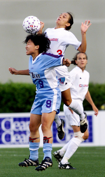 Atlanta Beat's Sun Wen, left, #9, gets the header despite an attmept by Carolina Courage's Staci Burt, center, #3, to get control of the ball June 2, 2001. The Beat lost to the Carolina Courage 2-0 at Georgia Tech's Bobby Dodd Stadium.