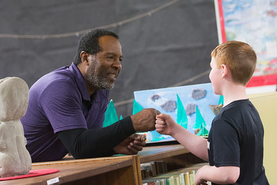 Hamilton Elementary School custodian Mike Daniels fist bumps a student after lunch March 28, 3.18. (Jesse Major/Peninsula Daily News)
