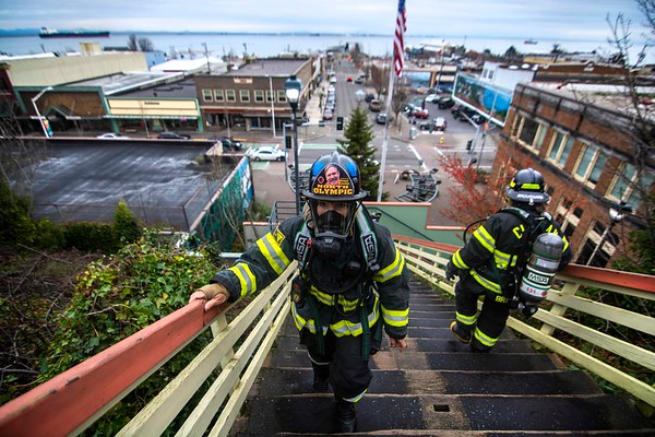 With a photo of her late father-in-law Richard Brueckner attached to her helmet, Clallam Fire District No. 2 Firefighter Margie Brueckner climbs stairs Dec. 1, 2019 in downtown Port Angeles. Firefighters across the North Olympic Peninsula are preparing Leukemia and Lymphoma Society Firefighter Stairclimb scheduled for March 8, 2020. (Jesse Major/Peninsula Daily News)