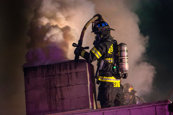 Firefighter Doug Eaton of the Port Angeles Fire Department sprays down the chimney of Sunrise Meats in Port Angeles Nov. 25, 2018. (Jesse Major/Peninsula Daily News)