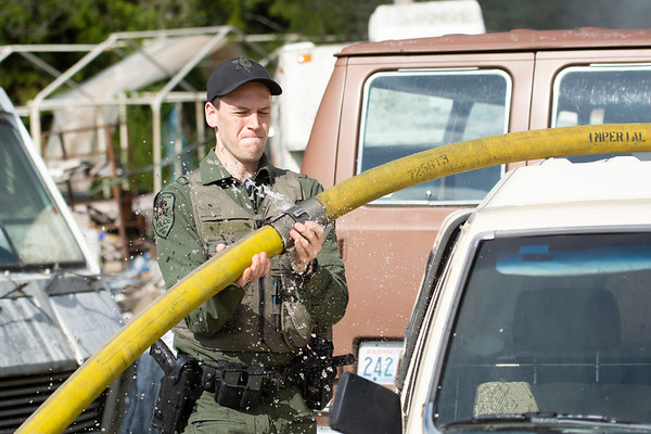 Lower Elwha Klallam Police Officer Dylan Heck lifts a hose over a vehicle as firefighters from Clallam Fire District No. 2 battle a blaze on the 200 block of Kacee Way April 24, 2019. (Jesse Major/Peninsula Daily News)