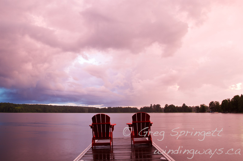 Sunset cottage dock muskoka chairs rain storm