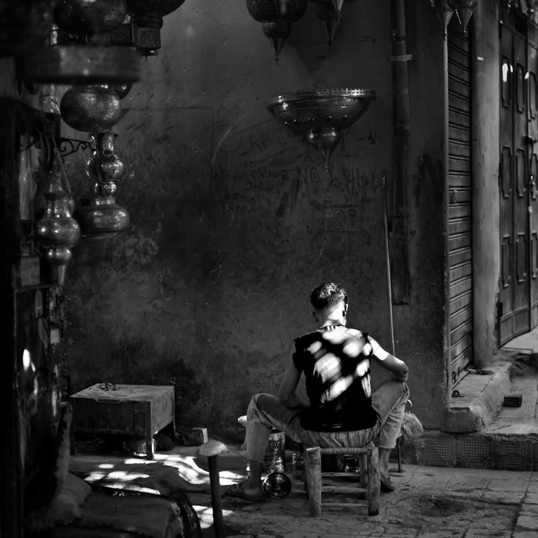 Photograph: Worker in the Souk - Monochrome travel photograph of a man working in the souks of Marrakech, Morocco.