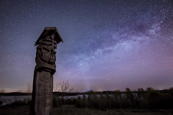 Photograph: Guardian of the Night - A wooden totem pole underneath the Milky Way by Lake Galvė in Trakai, Lithuania.