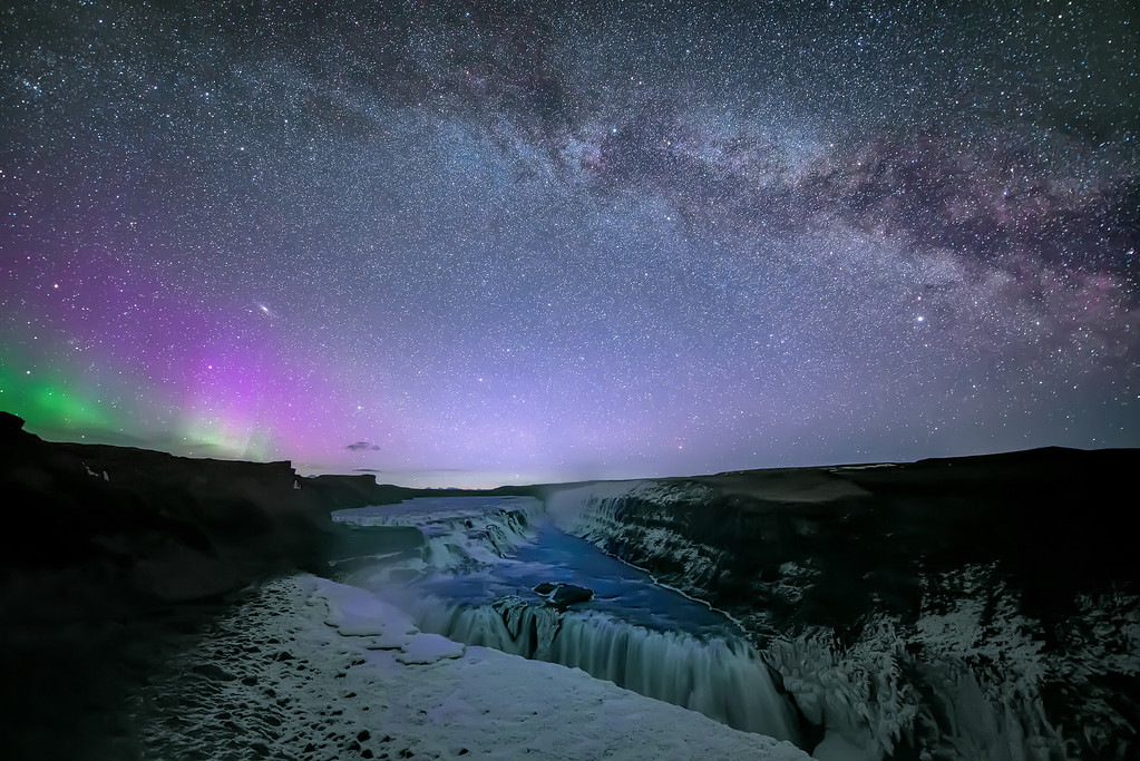 Photograph: Where Galaxies Meet - The Milky Way and Aurora Borealis over Gullfoss waterfall in Iceland.