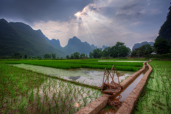 Photograph: Rice Harness - Photograph of sun rays bursting through the clouds over the rice fields and karst mountains of Yangshuo in South China.