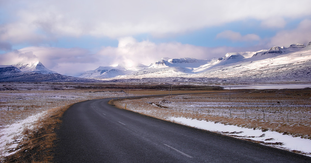 Photograph: Journey to the centre of the Earth - Road in Iceland, leading off to the snow-covered mountains in the distance.