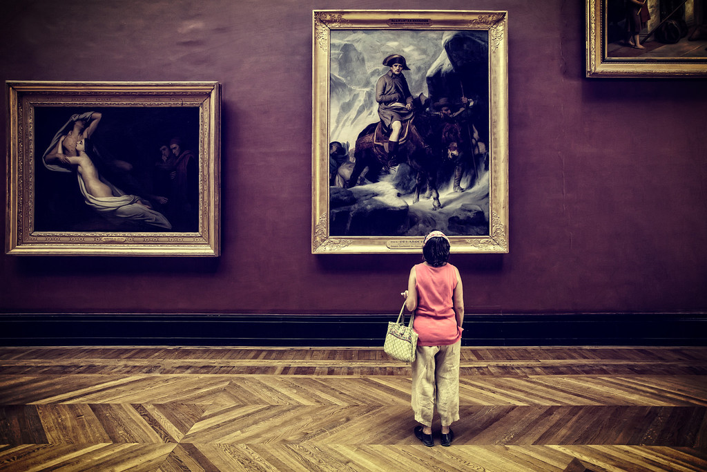 Photograph: In Awe of Art - A lone woman stands admiring some paintings in the Louvre Museum in Paris, France.