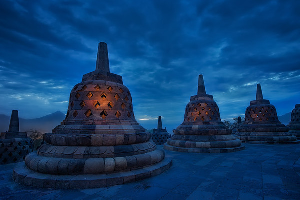 Photograph: The Blue Temple - Sunset blue hour shot of the stone bells stupas at Borobudur Buddhist temple in Indonesia.