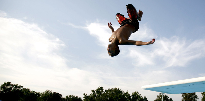 Tyler Johnson, 12, of Mattoon, performs an 'old school' gainer off of the diving board at Lytle Pool in Mattoon, Illinois on Monday, July 21, 2008. Johnson frequents the pool often and thinks it is a great way to cool off on hot days.  (Jay Grabiec/Staff Photographer)
