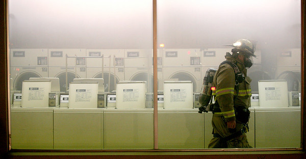 A Mattoon fire fighter walks through a laundromat located at 12th and DeWitt in Mattoon, Illinois on Monday, January 12, 2009.  The fire was caused when a large dryer caught on fire while in use.  (Jay Grabiec/Staff Photographer)