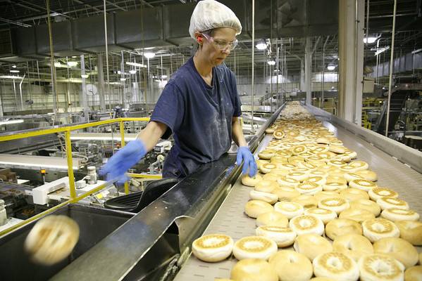 Bagel inspector Beth Stevens discards a bagel that does not meet the standards of identity at the inspection point of production at the Lenders Bagel factory in Mattoon, Illinois on Wednesday, July 16, 2008.  (Jay Grabiec/Staff Photographer)