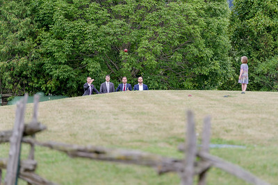 A groom plays bocce with his groomsmen after a wedding in Prince Edward County